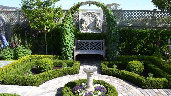 """A combination of hardscaped pathways, architectural elements, and boxwood hedges, this stately garden in Orange County, California, transports you to a classic English garden. """"The design was entirely the vision of the homeowner,"""" says Rick Remington of Remington Construction Services. """"It was my task to turn those thoughts into something tangible."""" Though the hedges might seem high maintenance, an electric clipper keeps them in tip-top shape — without requiring a professional gardener."""