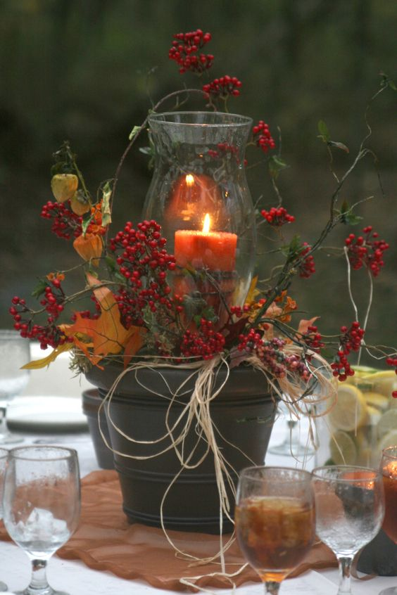 DIY fall wedding centerpiece. Oil rubbed bronze spray painted clay pot, hurricane globe, leaves, Chinese lanterns, bittersweet and other berries and vines gathered in the woods, raffia ribbon.