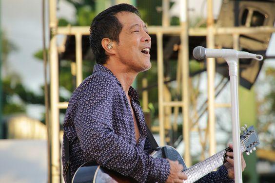 ブルーのシャツを着てステージで歌っている矢沢永吉の画像