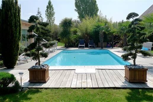 Aménagement paysager autour d\'une piscine avec une terrasse en bois ...