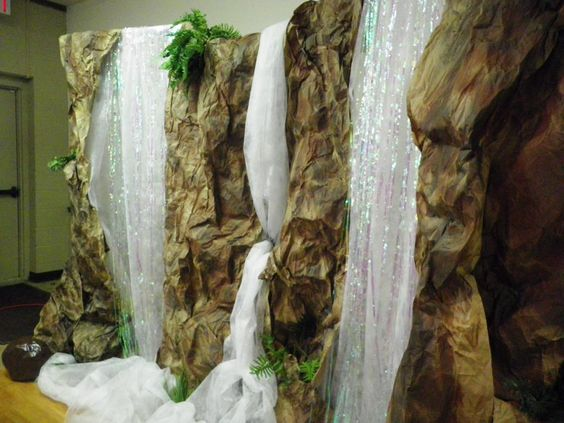 "faux Water Falls for a set -- made using a PVC pipe frame. Add crumpled brown paper that has been sprayed w/ brown & black paint, some irridescent-metallic door curtains & white gossamer or nylon tulle for the fountains & water fall (plastic cling wrap also works). Paper mache' rocks made from bags filled with crumpled newspaper (use liquid starch for the paper mache). Spray paint when dry. A few pieces of greenery tucked into the paper give it a ""woodland falls"" vibe:"