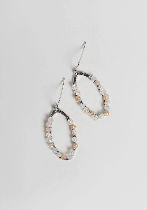 These adorable silver-toned earrings feature a hanging design with an oval-shaped cutout.