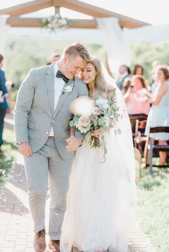 This mountain wedding featured an a-line dress with lace and tulle, the groom in a light gray linen suit with a charcoal bow tie, and an arbor with tulle and a rose and greenery floral feature. The bride's bouquet was a gorgeous Neutral and blush tone with fluffy peonies and roses! Click the link to see the full wedding! #love #wedding #weddingideas #weddinginspiration #bouquet #weddingbouquets #diywedding #weddingdress #weddingdresseslace