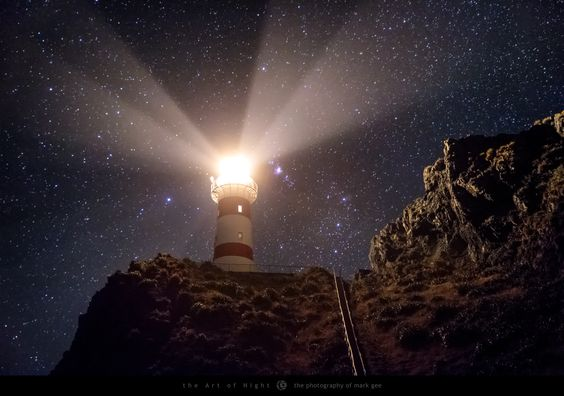 Night Light - The Cape Palliser Lighthouse on the southernmost point on the North Island of New Zealand sits perched high on top of a cliff with a 280 step climb to get to it. The light of the lighthouse rotates once every 20 seconds, which makes it a great subject to photograph at night during a long exposure.  In this shot you can see the constellation of Orion sitting between the cliff face and the lighthouse, and the Orion Nebula (M42) can be seen right next to the lighthouse light. The…