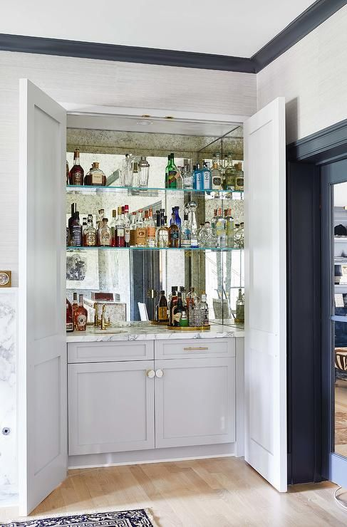 Hidden Behind Light Gray Double Doors Glass Shelves Are Mounted Against A Smoked Mirror Backsplash And Over Living Room Bar Home Bar Cabinet Home Bar Designs