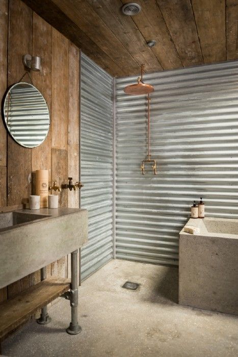 Cabin | Corrugated tin bathroom is separated by a sliding steel barn door