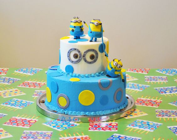 Minions- Despicable Me Cake frosted with Swiss Buttercream and accented with fondant circles.  Minions are made from fondant.