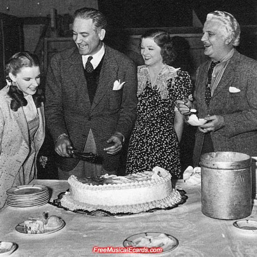 A much happier moment. Smiles all round as Judy Garland, Victor Fleming, Myrna Loy and Frank Morgan enjoy the celebration on the set of The Wizard of Oz. Judy Garland must be hungry for a piece of cake!: