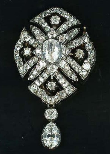 A late Victorian diamond brooch, circa 1880, the central pear-shaped diamond, to an openwork quatrefoil border set with cushion-shaped and old brilliant-cut stones, suspending a pear-shaped diamond swing drop, diamonds approximately 6.80 carats total, length 6.0cm.