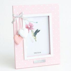 Un marco ideal para regalar a un bebé por su nacimiento o para su Bautizo.   Es de madera lacada en rosa o celeste con lunarcitos blancos. Lleva unos corazones de madera o unas estrellas colgando.  Lo podemos grabar con el nombre del bebé, lo hacemos en el momento!!