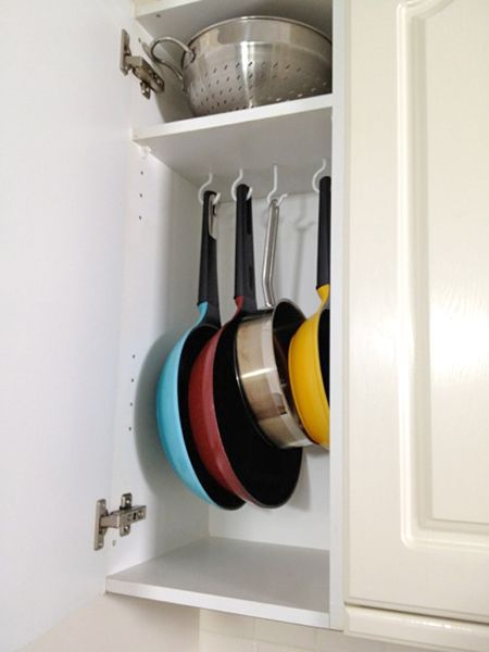 A neat way to store your pans is with screw-in cup hooks. For an overhead cabinet, line them up on the underside of a shelf, spacing them apart enough to ensure they'll each be easy to access.: