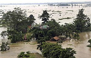 A helicoper distributes relief materials at a flood hit area in Sonitpur, India.  (AP Photo)  01/07/2012