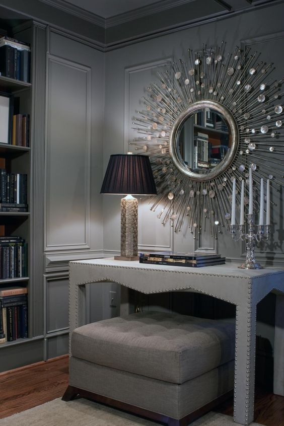LOVELY!  This corner is accented by a custom upholstered table and sparkling accessories. The silver mirror, lamp base and candelabra shine against the soft gray palette. The ottoman is stored under the table until it is needed.