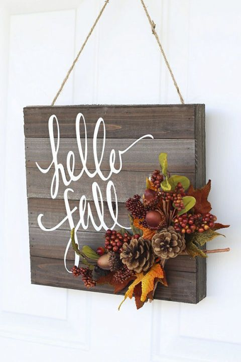 """Branch out from the traditional wreath with a door hanger that displays the season's greetings — or gear your message toward Thanksgiving with a simple """"Give Thanks."""" Plus, all it takes to make this pretty door decor is a wooden board and some paint. Click through for a tutorial and more homemade fall wreaths."""