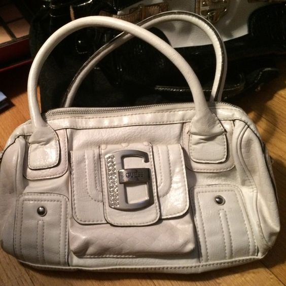 White genuine guess bag, relatively small. 3 inside pockets; 1 of which has a zipper, no stones missing from guess symbol on front. One compartment on front of bag that buttons. Worn only a few times, good condition. Willing to negotiate but no trades unless they are guess. Lmk if anyone has questions :) Guess Bags Mini Bags