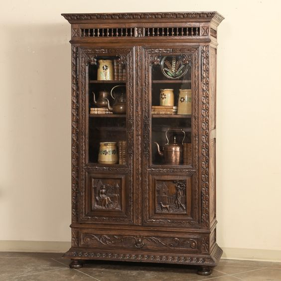 Featuring all the charm of the lush, rolling countryside and endless miles of seashore, Antiques from  Brittany like this wonderful Vitrine (curio cabinet) would be the pride of any family, housing and displaying their most cherished heirlooms and prized collections.  This example features the typical carved embellishment on indigenous white oak, with a decided Renaissance style flair and rural scenes in full relief on the lower panels.  Boldly carved moldings and cornerposts complete the…