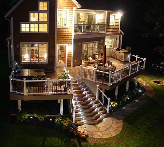 Custom Composite Deck.  Master bedroom level deck overlooks 800 square foot deck that has it all:  hot tub, outdoor kitchen, gas fire pit, natural stone walk way and fabulous low voltage LED lighting by I-Lighting, LLC.  All decking, rails, trim are Fiberon Horizon.
