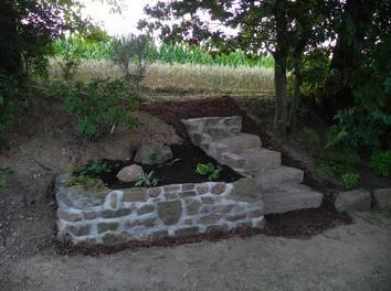 Eine Sandsteinmauer hilft gegen Steinchen im Rasenmäher.