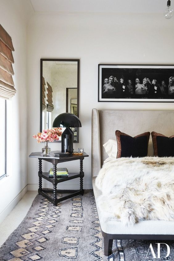Kourtney Kardashian's bedroom with a vintage rug, a nude headboard, and a faux fur throw blanket: