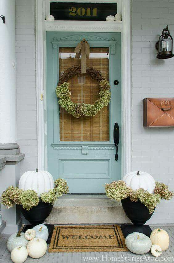 Gray house with aqua door, dried hydrangea wreath and under white pumpkins