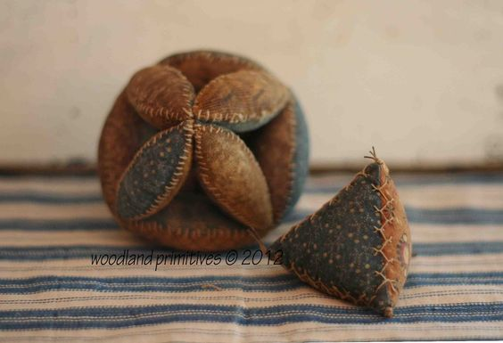 """Woodland Primitives: This amish puzzle ball was created using 18 different fabrics & has wonderful detail stitching around every segment, it's 3"""" in diameter. The amish triangle pinkeep is filled with crushed walnut shells & has decorative stitching on every seam. Each side is a different civil war reproduction fabric, it is 2"""" high."""