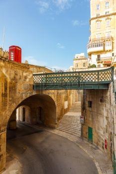 Traditionelle schmale Stra�e, alte H�user, Bogen-, Tunnel-und Fu�g�ngerbr�cke in Malta. Malteser Architektur in Valletta, Malta photo