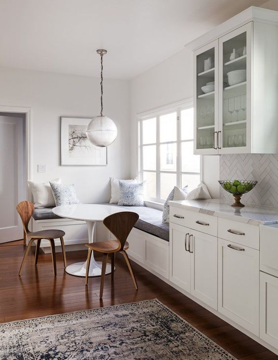 white dining space and kitchen // globe pendant light // hardwood floors // corner bench // white cabinets