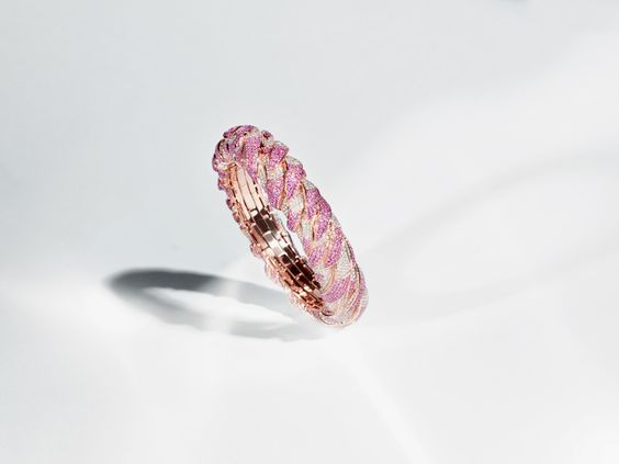 Bracelet Flamingo Embrace. Des sapphires roses et diamants blancs dessinent les plumes d'un flamant rose. Le mécanisme 'stretch' unique de ce bijou lui permet de s'étirer afin de s'adapter à toute taille de poignet. © Nirav Modi  Flamingo Embrace Bangle. Layers of flamingo feathers are painted with pink sapphires and white diamonds. The unique mechanism of the jewel allows it to 'stretch' to fit any wrist size. © Nirav Modi