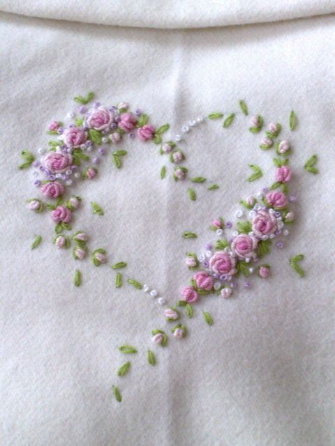 The leaves are detached chain stitches, the buds are french knots, and the roses are lovely examples of bullion stitch.
