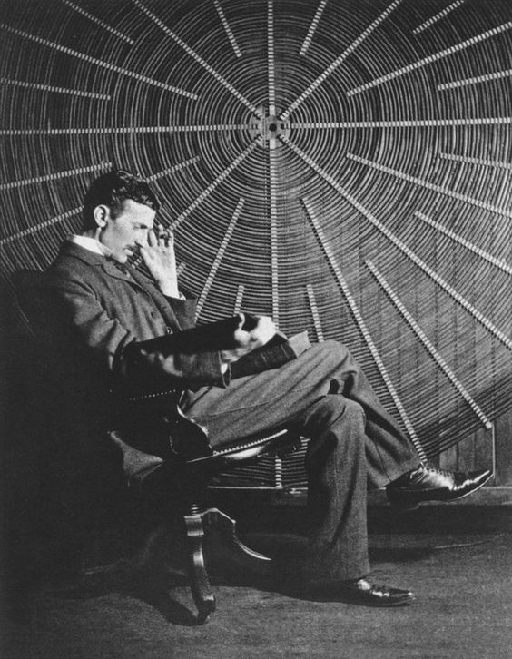 """drnikolatesla: """" Nikola Tesla reading James Clark Maxwell's book, """"The Scientific Papers,"""" given to him as a gift from his good friend Sir James Dewar. Tesla sits in front of the spiral coil of his high-frequency transformer at East Houston St. 46,..."""