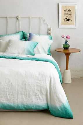 Modern tie dye linen with the edges of a white bed linen set dipped in aqua dye