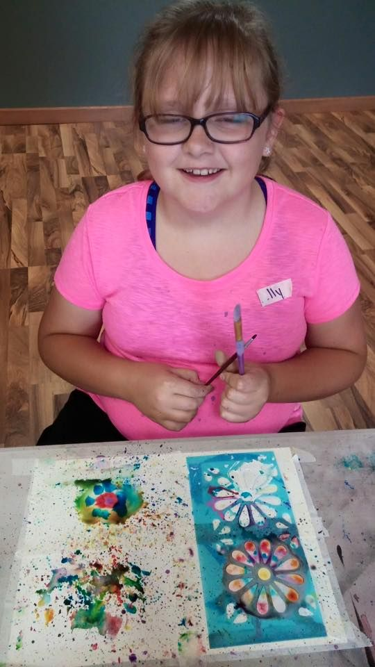"7/26/15.  Monticello's Erin's art camp encompassed the exploration of watercolor and acrylic. We experimented with different techniques and textures...and we had fun doing it! Kelly trying her hand at using a stencil with the ""splattering"" or ""tapping"" technique. Loving the dream-like flowers!"