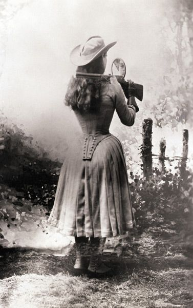 Annie Oakley shooting over her shoulder using a hand mirror.