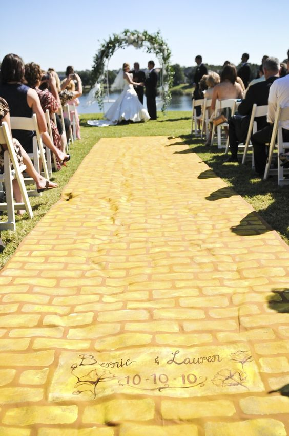 Hand painted yellow brick road aisle runner. Custom brick at end with wedding date Lauren's Wizard of Oz themed wedding. Wedding Dress and bridesmaids' corsets by Castle Corsetry themarriedapp.com hearted <3