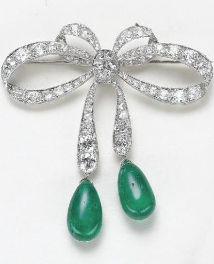 A Diamond and Emerald Bow Brooch  Designed as an old-cut diamond bow, suspending 2 cabochon emerald drops, mounted in platinum and white gold, length 2 1/4 inches.