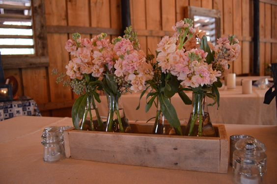 blush and apricot colored stock in simple bud vases and wooden box for a rustic wedding centerpiece.