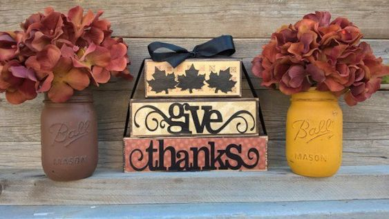 one orange and two yellow boxes, stacked on top of each other, tied with a black ribbon, featuring leaves and the words give thanks, placed on wooden steps, near two mason jars painted in brown and yellow and containing red flowers
