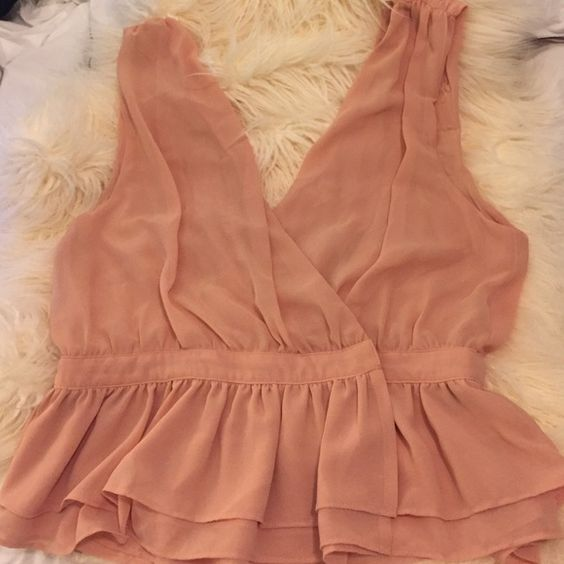 Sis Sis wrap top Very cute low cut blush wrap top. Ruffles at the bottom of the top. Size Large. Top goes with anything. Sis Sis Tops Tank Tops