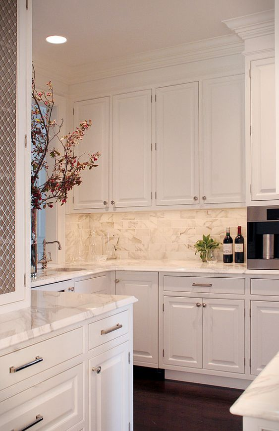White calcatta on the countertops blends in perfectly with the same on the walls. When you add in white cupboards, you have a clean and fresh looking kitchen all the way around.