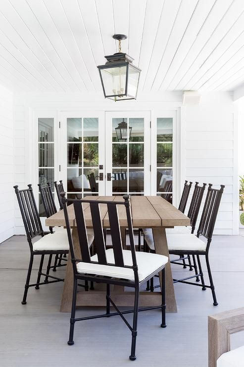 Brown Outdoor Dining Table With Black Metal Dining Chairs In A Covered Patio Space Boasting Outdoor Dining Spaces Metal Dining Chairs Outdoor Tables And Chairs