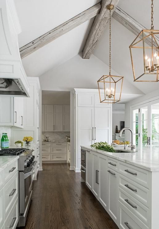 Chic kitchen boasts a gray vaulted ceiling adorned with gray wood beams over a white shaker cabinets paired with calacatta marble.: