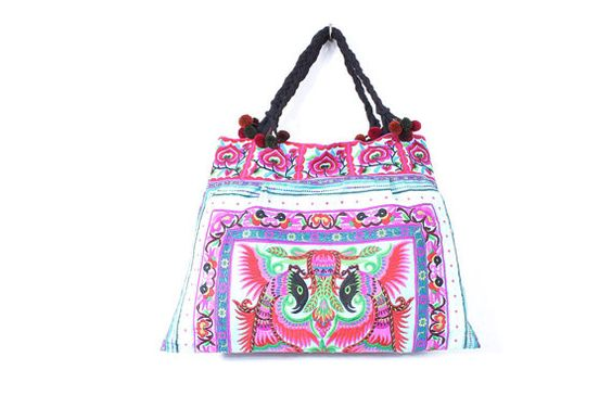 Bright and beautiful tote bag made with a piece of fabric from the HMONG Hill Tribe of Northern Thailand. It features pom poms and a zipper closure. #ethniclanna #vintagefabric #handbag #tote #totebag #unique