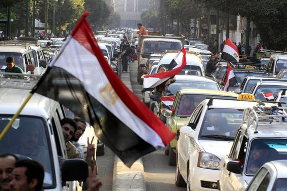Egyptians wave national flags outside their vehicles during a traffic jam headed to Tahrir Square in Cairo, Egypt, Saturday, Feb. 12, 2011.