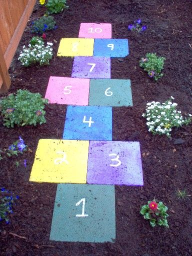 """Hopscotch made with pavers in garden or backyard.  Made by purchasing 12""""x12""""x2"""" smooth gray stepping stone.  Simply paint with a product such as Patio Paint, intended for terra cotta pots that stay outdoors in whatever colors you want.  Be sure to dig 3 inches down to allow for paver sand so stones will lay smoothly."""
