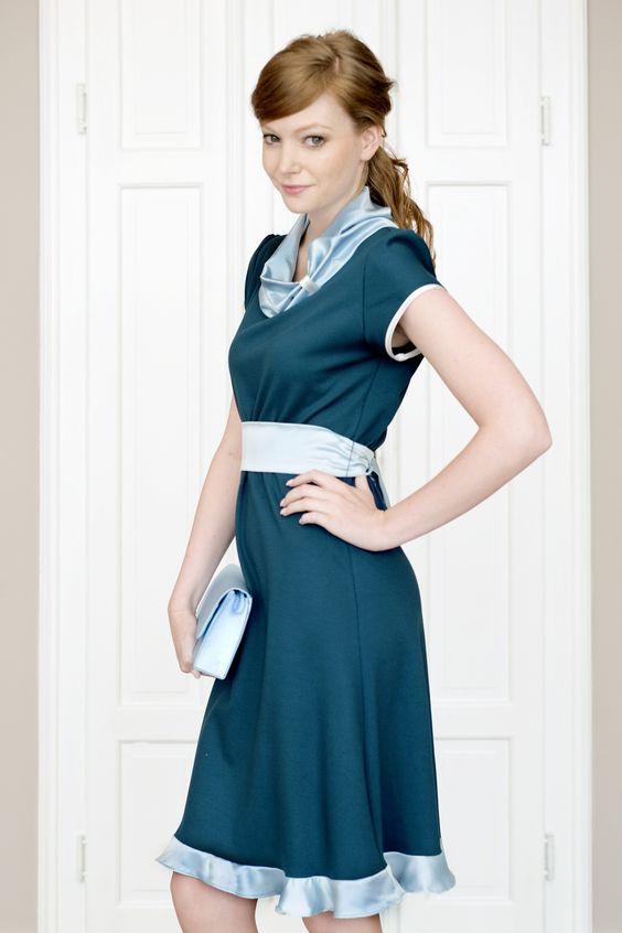 Labude - Kleid Delphine ist ein petrolfarbenes, ausgestelltes Kleid aus weich fallendem Jerseymaterial mit türkisfarbenem Kragen, Gürtel und zarten Saumvolants