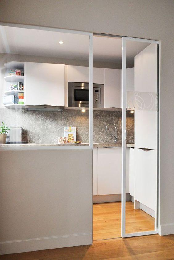 La bonne idée de cet appartement de 31 m2 ? L'installation d'une porte coulissante dans la cuisine pour ne pas perdre d'espace et faire rentrer la lumière ! Plus de photos sur Côté Maison http://bit.ly/1NdYQwl: