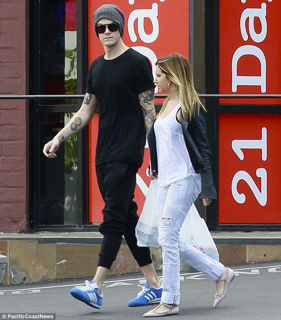 Rocker chic: Christopher donned an all-black ensemble with a grey beanie and blue shoes, as Ashley wore a loose white shirt, tattered jeans,...