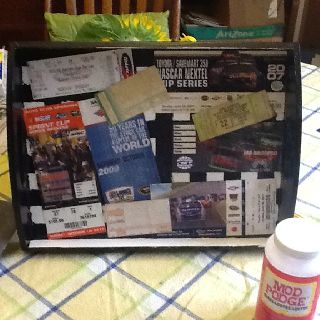 Mod podged racing ticket stubs on a wood tray I painted black fr my hubby. He will use to eat peanuts while watching his Nascar!