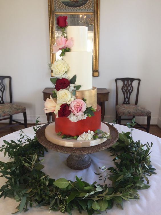 Magpies Bakery Knoxville, TN  Four tier buttercream wedding cake with red and gold block color tiers finished with beautiful cascading floral.  Magpies Bakery  Knoxville, TN Venue: Crescent Bend