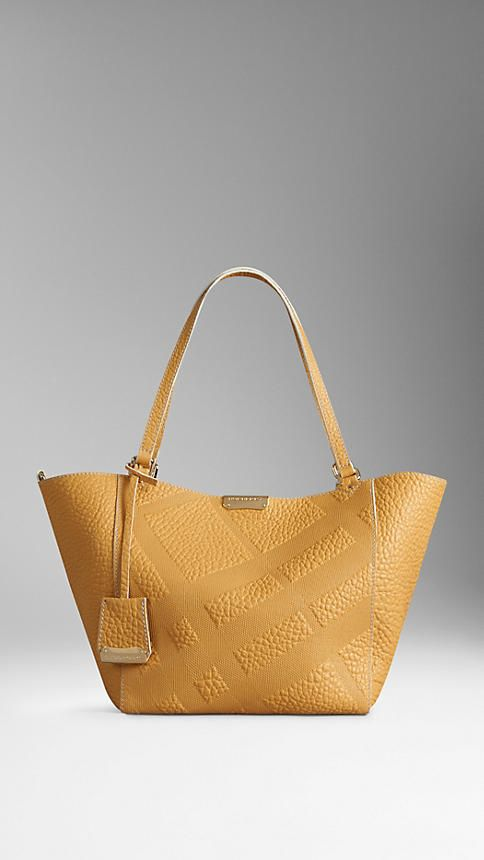 The Small Canter in Saffron Yellow Bonded Leather from Burberry -A tote bag in signature grain leather with embossed check panels, bonded to contrast colour nappa leather at the interior. The design features slim straps and a leather tag, while the open top closes with a magnetic press stud and stay fastening. Discover the women's bags collection at Burberry.com